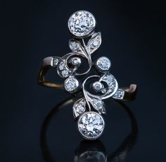 Antique Art Nouveau Diamond Flower Ring, Circa 1900. A silver over 14K gold ring of a floral design in Art Nouveau taste is bezel-set with old European cut diamonds.