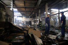 Una de las fábricas incendiadas es revisada por obreros.