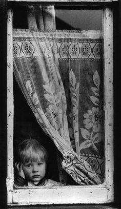 Little Boy Stares Out of a Window, Salford, Manchester, 1962 by Shirley Baker.