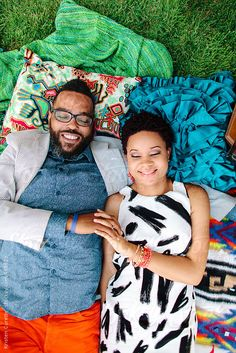 A hipster African American couple laying on blankets in the park by poorartist | Stocksy United
