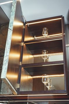 INTERIOR-iD - Mayfair Kitchen. The tall bronze unit is effectively a fine storage unit with its pull-out plate racks and leather lined shelves, which have been lit up with defused LED lighting
