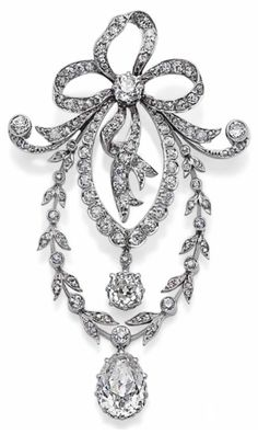 A BELLE ÉPOQUE DIAMOND, GOLD AND PLATINUM PENDANT. Of ribbon and garland design, set with old-cut diamonds, mounted in platinum and white gold. Circa 1910.