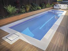 An elongated  plunge pool  designed for lap swimming, this sleek jewel features a Q-pebble navy lining with blue glass mosaic waterline tile inlay along the rim. The Himalayan sandstone coping and Merbau timber decking and border further enhance the visual impact.