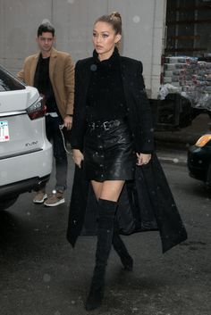 Gigi Hadid wearing a skirt from The Kooples, a Blaq sweater, and Stuart Weitzman over-the-knee boots.