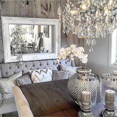 Love the combination of the rustic table and wood wall with the glamorous chairs, pillows, and chandelier! Lovely!