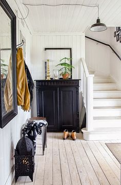 Modern farmhouse style with white beadboard farmhouse entry hall with wood stairs and black cabinet.