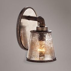 Tea-tone seedy glass lends a distinctive look to this chic industrial wall sconce.