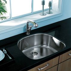 single bowl kitchen sink with a spoon and a cup of coffee