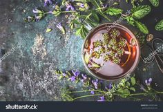 Cup of herbal tea on dark aged rustic background, top view, place for text, border