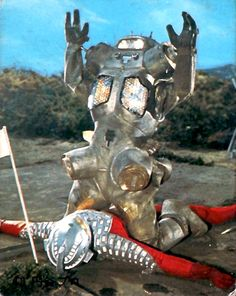 ultraman in a fix again? oh yes! feel the pain. robot metal hurts the face.