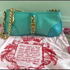 Juicy Couture Aqua Blue Leather Bag Wristlet Clutc In excellent condition.  Outside is a soft aqua blue leather with a gold chain and heart lock. It closes by a metal zipper with the classic J zipper pull. Strap is a chunky gold chain. It can be removed from one side of the bag by a lobster claw & attached to the other side of the chain to convert the bag into a wristlet/clutch.  There is an inside zippered compartment with the classic gold J zipper pull. Includes original Juicy dust bag…