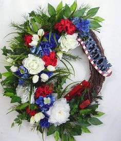 """This beautiful Patriotic July 4th door wreath sets on a nature grapevine wreath base.  The wreath is embellished with lots of Greenery, beautiful white Peony and Roses, blue Hydrangea, white Tulips, and red Hydrangea. The wreath is accented with a Freedom sign and a red airplane.  The wreath measures from tip to tip at 26"""" (L) x 24"""" (W) x 7""""(D)."""