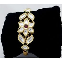 An attractive kundan bracelet, combination of green, maroon and gold with studded ac kundan, gives a very royal and elegant look to you wrist, a must with indian ethnic attires.