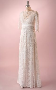 Anna by Martin McCrea   All-over guipure lace wedding dress with empire waist and mid length sleeves. Satin button detail down each sleeve and back of gown. Available in plus size and custom sizes.