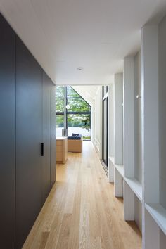 This hallway features exposed painted wood studs that act as alcoves for hanging coats. #Hallway