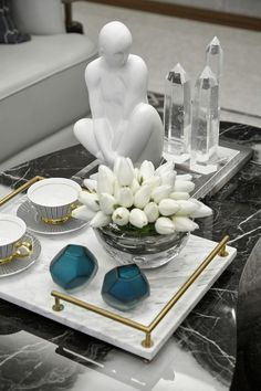 A formal tablescape on coffee table w/ black marble top. Layered w/ contrasting white marble tray w/ gold-finished handles. Gold accents repeated on coffee cups. Clear, glassy material of vase, Centerpiece Decorations, Decoration Table, Table Centerpieces, Coffee Table Decorations, Green Decoration, Decoration Crafts, Coffee Table Styling, Decorating Coffee Tables, Home Decor Styles