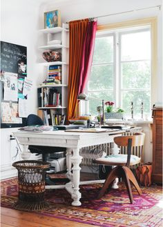 chunky white antique table turned desk with a modern chair and Indian rug