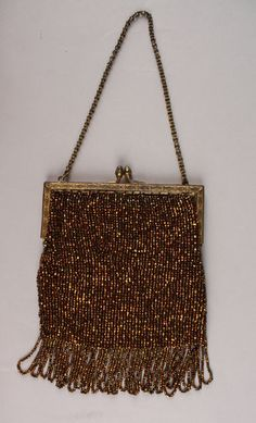 Date Made: 1900-1930  Description:  Purse; iridescent copper beads, looped fringe. Completely beaded in iridescent copper colored seed beads. Looped fringe along bottom edge. Goldtone frame with a floral design with an acorn clasp. Chain handle. Lined in gold silk.