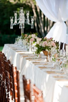 The head table will feature two tall crystal candelabras flanking a gold compote vase filled with cream hydrangeas, hot pink tulips, fuchsia garden roses, blush spray roses, white stock flowers, white lilacs, jasmine vine, and greenery with tall fluted votives with floating candles in pink water and gold mercury glass votives.