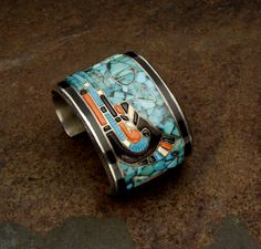 Cuff | Preston Monongye (Mission/Hopi).  Sterling silver with water serpent design in Turquoise, jet, coral and white shell.  ca. 1975.