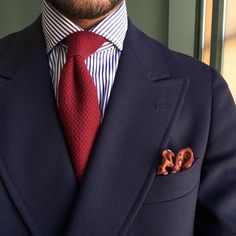 Double-breasted navy blazer, white shirt with blue candy stripes, red tie