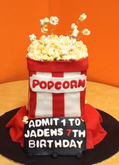 Popcorn Cake...Bottom is white cake filled with chocolate chip buttercream covered in buttercream icing and buttercream fondant.  Top cake is red velvet  filled with buttercream covered in buttercream icing and buttercream & marshmallow fondant with hand painted marshmallow popcorn made by Sugared Cakes & Bakes #moviepartycake #popcorncake