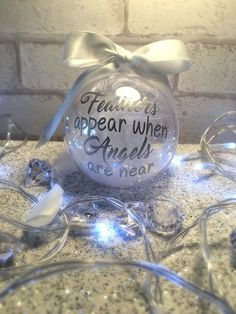 Stunning 8cm Clear Acrylic personalised bauble will make your christmas tree really stand and make the perfect keepsake. these are filled with crystal clear and coloured diamantes & your choice of coloured feathers & ribbon. Feathers appear when angels are near.... Can also be done with a single name see my other listings. Ribbon Choice: Purple, Blue, Black, White, Pink, Yellow, Silver, Red Feather Choice: Purple, Blue, Black, White, Pink, Yellow, Red Simply choose your text and colours ...