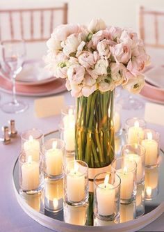 Martha Stewart wedding centerpiece ideas, have a candle for each guest as a parting gift. Love the simple look with all the same flower, and their stems showing! Clean and classy.