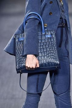 A total blue outfit with jacket, pants, leather bag