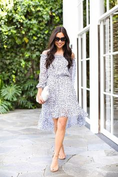 Kat Tanita of With Love From Kat wears a DVF silk off the shoulder dress with Stuart Weitzman nudist sandals and a white Lauren Merkin clutch in LA.