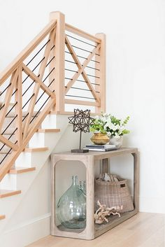 Wall Console. Staircase wall console ideas. Beautiful foyer features a curved wood console filled with recycled glass bottles, hammered gold bowl and a white vase filled with flowers lining a staircase wall. Ashley Winn Design.