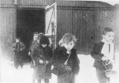 Soon after liberation, surviving children of the Auschwitz camp walk out of the children's barracks. Poland, after January 27, 1945. — US Holocaust Memorial Museum
