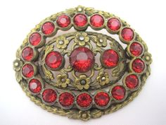 A stunning vintage red Czech glass brooch with marcasite accents. The setting is brass with small flowers. The glass stones are a very pretty deep