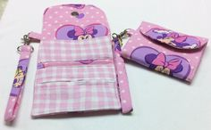 "Minnie Mouse Wrist Wallet. Minnie Mouse: A tri-fold wallet in a pink Minnie Mouse fabric. The wallet measures 4"" wide by 3.5"" high closed (4"" wide and 9.5"" high open) and has a magnetic snap closure. Wrist strap is approximately 5.5"" long and attaches to the wallet with a lobster swivel hook. (Wrist strap is removable.) One interior zippered pocket (for holding coins and cash) with an open slot for ID and credit cards.. Machine washable."
