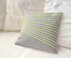 Linen pillow cover in silver gray with white and neon yellow stripes -Surfing with fabrics-. €20,00, via Etsy.