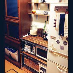 最上段をすのこで便利な作業台に  低めのスチールシェルフにブライワックスを塗ったすのこを載せ、最上段は作業台に。盛りつけたり、仮置きしたりする場所があると、キッチンの作業がはかどります。ウォールラックとすのこの色があっているので、ディスプレイスペースが引き立ちますね。