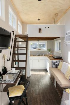 """The living room features a 27"""" x 80"""" built-in daybed/couch with storage underneath and a built-in bookcase stained to match the stairway."""