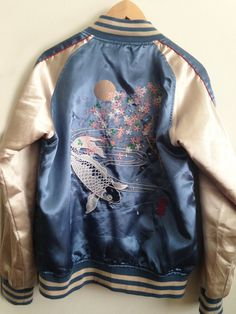 A unisex vintage Japanese bomber jacket. Features 2 front pockets and one inner jacket pocket. Lovely aqua blue/ivory color with red piping,