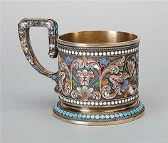 A Russian silver-gilt and cloisonne enamel tea glass holder, I. Saltikov, Moscow, 1899-1908 decorated with polychrome flowers and scrolling foliage on stipled ground, angular scroll handle 84 standard 6.5 cm high