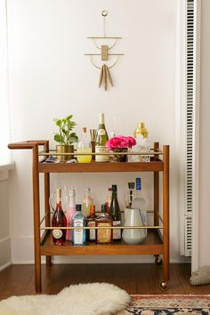 Bar cart: I like the idea of plants, pitchers, and bottles mixed together.