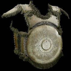 Ottoman krug, 15th/16th c, steel, circular chest plate with St. Irene arsenal mark and back plate with flat central boss bordered by radiating flutes, three smaller plates below the neck and under the arms by riveted and solid rings, back-plate with shoulder-defense and upper arm defenses, an articulated plate below on riveted leather, six smaller side plates all attached by riveted and solid rings, the main edges with riveted green cotton fringes, and domed copper rivets, 44.5 cm. high.