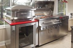 This is a beautiful and functional outdoor kitchen...refrigerator, grill, griddle and a pizza oven...a party waiting to happen! Love the red counters set to show off the gleaming stainless steel outdoor kitchen. The red counters are Red Shimmer by Caesarstone, Quartz. Photo by David Robinson Photography,
