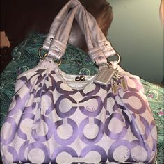 REDUCED!  Authentic Coach Parker Handbag This is an amazing handbag. I love it dearly but it is just hanging on my rack & isn't being used. She needs a new home where she is used frequently! It is in new condition. It has three compartments w/ the middle one being a kisslock closure. ItIt is grey/silver and lilac signature print. This is a large bag. & the pictures really don't do it justice. I also have the matching trifold w/checkbook wallet. please make an offer! For both pieces I will…