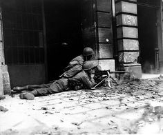 GI machine gun crew in action against German defenders in the streets of Aachen on 15 October 1944