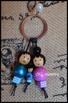 Porte-clés poupées perles bois, verre et plastique thème famille. Peut aussi être utilisé en bijoux de sac à main. Les perles en bois sont peintes et vernies à la main. Hauteur poupées 5 cm (papa), 6 cm (maman) , 2,5 cm (enfant), hauteur total avec porte-clés 11 cm. Fait main. Le porte-clé est livré dans une jolie petite boîte.