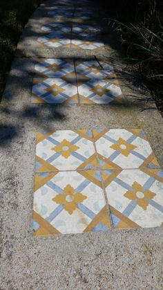 Patterned cement tile placed in a poured cement walkway adds interest.
