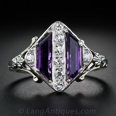 This unique and striking Art Deco ring, circa 1930s, is a work of jewelry art in purple and white - amethyst and diamonds that is. The lozenge shape top is set with a pair of trapezoidal amethysts bisected  with a sparkling row of tiny single-cut diamonds with a single diamond twinkling on each corner. The shoulders are adorned with graceful open work and hand engraving continuing down the ring shank. A splendid and singular vintage ring. Limited sizing available on this petite ring.