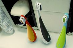 Upstanding toothbrush makes use of a weight at the end of its rounded handle to create a centre of gravity at the handle base.