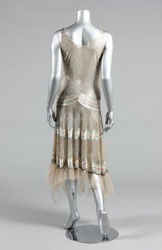 A beaded tulle flapper dress, circa 1929-30, the ground entirely covered in a tight lattice of silver bugle beads with pastel beaded bands to the skirt and a beaded bow motif to the V neck, the hem edged in nude tulle, bust approx 86cm, 34in Provenance: Henning Thorsen collection
