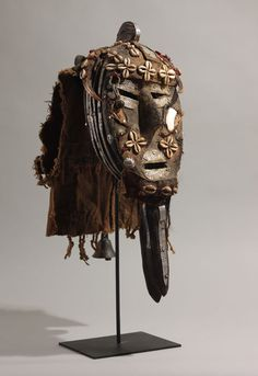 Poro Society Mask (Loma/Toma, Liberia/Guinea) Wood, brown and red cloth, white metal, mirrors, horns, cowries, bell, 23 ½ in, na